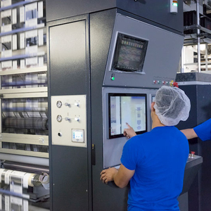 employees operating packaging machine on factory floor